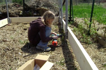 ella helping to build a greenhouse
